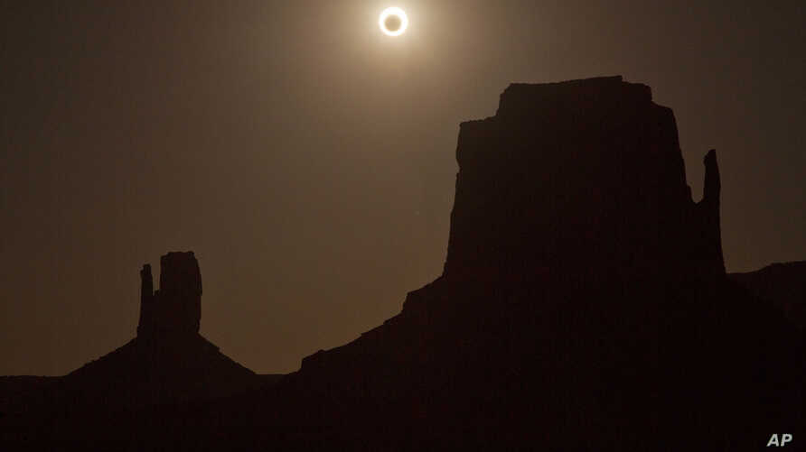FILE - The new moon crosses in front of the sun creating an annular eclipse over West Mitten, left, and East Mitten buttes in Monument Valley, Arizona, May 20, 2012.
