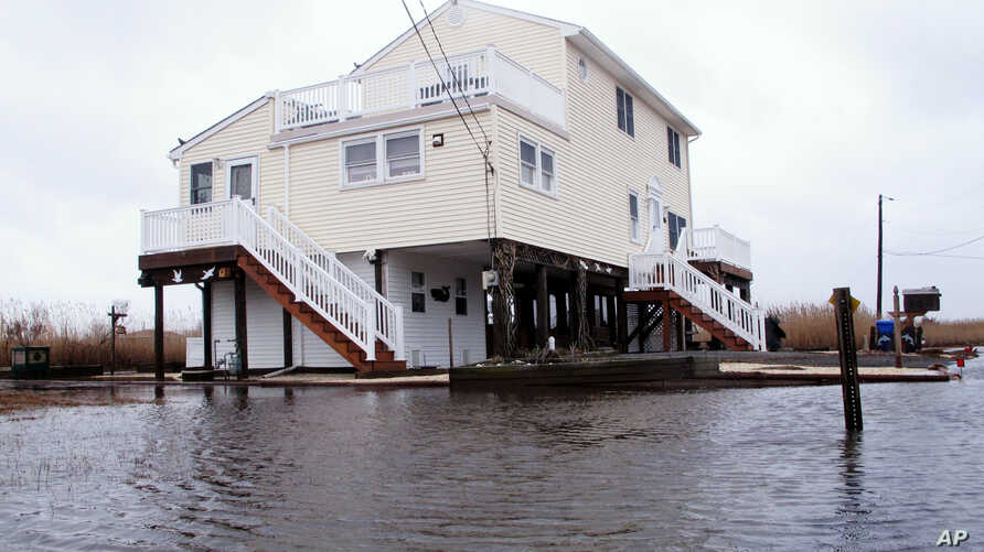FILE - This March 14, 2017, photo shows Jim and Maryann O'Neill's home in a back bay neighborhood of Manahawkin, N.J., surrounded by water after a moderate storm.