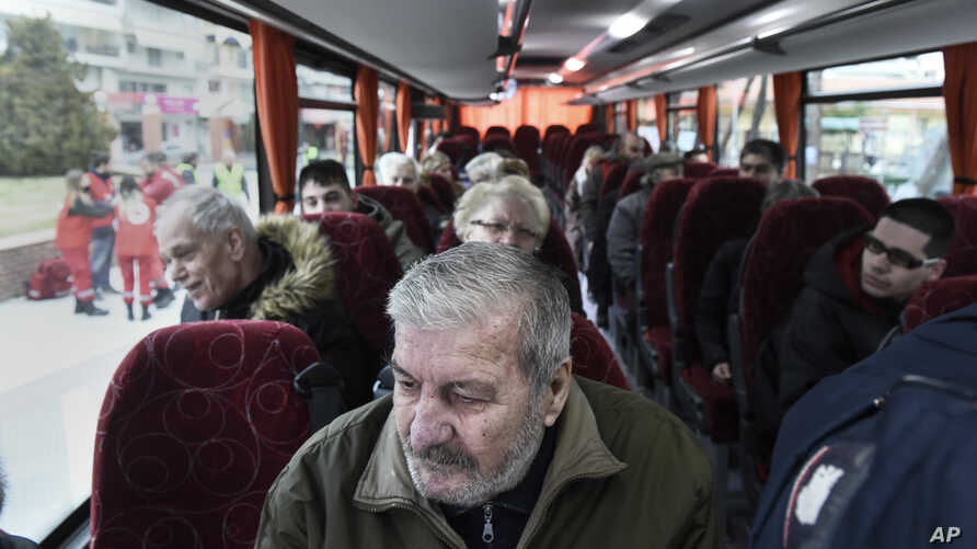 Residents of Kordelio district are taken away by bus after authorities ordered the area evacuated in order to defuse a 500-pound unexploded World War II bomb, in Thessaloniki, Greece, Feb. 12, 2017.