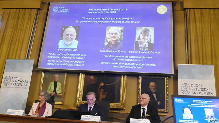 Members of the Nobel Committee for Physics sit in front of a screen displaying portraits of Arthur Ashkin of the United States, Gerard Mourou of France and Donna Strickland of Canada during the announcement of the winners of the 2018 Nobel Prize in P