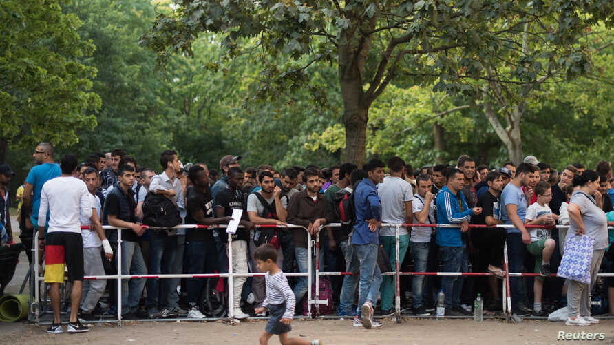 Newly arrived migrants wait in front of the State Office for Health and Social Affairs to apply for asylum in Berlin, Germany, Aug. 11, 2015.