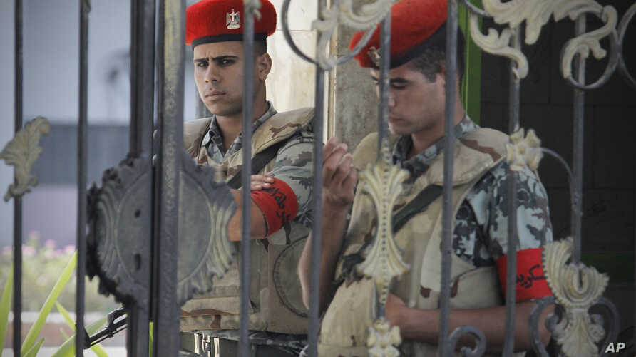 Egyptian soldiers stand guard outside the Maadi military hospital where former president Hosni Mubarak was transferred and is currently on life support, June 20, 2012.