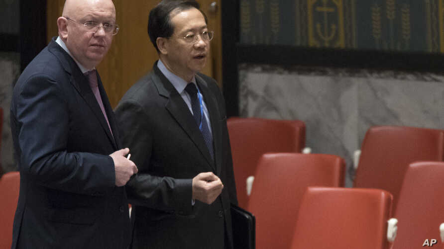 Russian Ambassador to the United Nations Vassily Nebenzia, left, speaks to Chinese Ambassador to the United Nations Ma Zhaoxu before a Security Council meeting on the situation in Syria, at United Nations headquarters, Feb. 23, 2018.