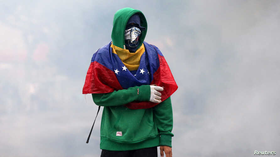 A demonstrator clashes with riot police while rallying against Venezuela's President Nicolas Maduro in Caracas, Venezuela, April 13, 2017.