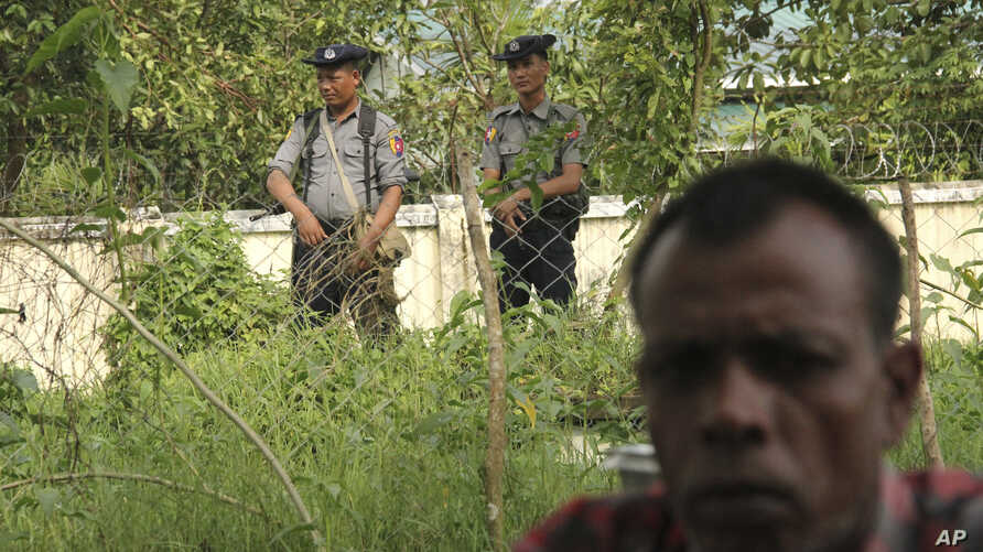 FILE - A Hindu man sits, seeking shelter, after fleeing violence that broke out on Aug. 25, as soldiers keep watch, in Maungdaw town, Rakhine state, Myanmar, Sept. 6, 2017.