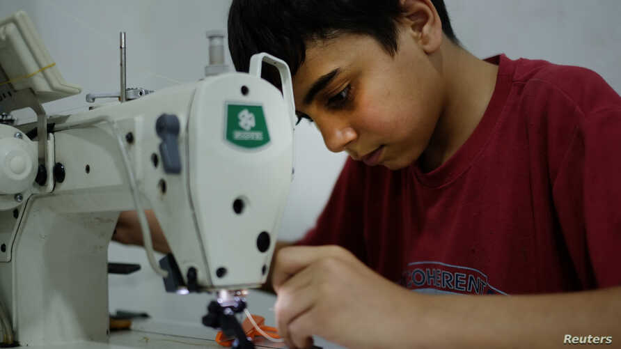 Syrian refugee child, Ahmad Abo Baker, works at a shoe workshop in Gaziantep, southeastern Turkey, June 2, 2016. Ahmad works 12 hours a day, six days a week along with his father. The boy rises at 7 am, goes straight to work and doesn't stop except f