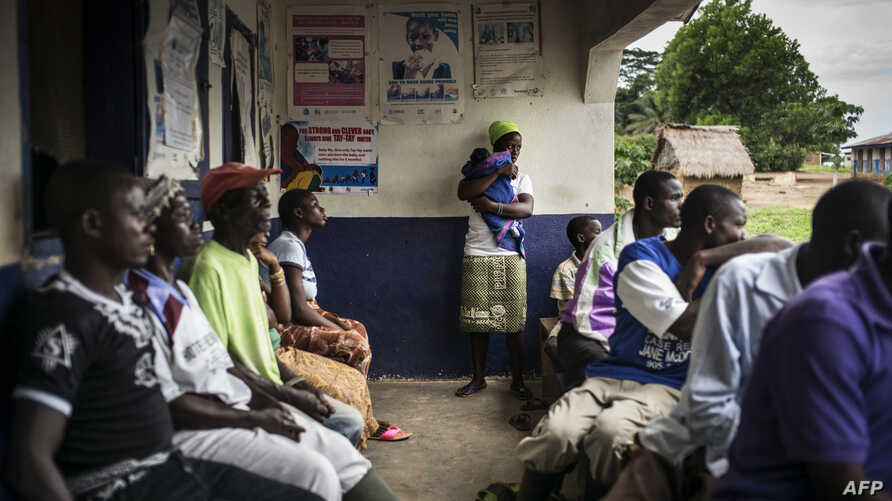 FILE - A mother holds her newborn in the remote health center in the Liberian village of Mendicorma, just across the border with Sierra Leone on April 27, 2016.
