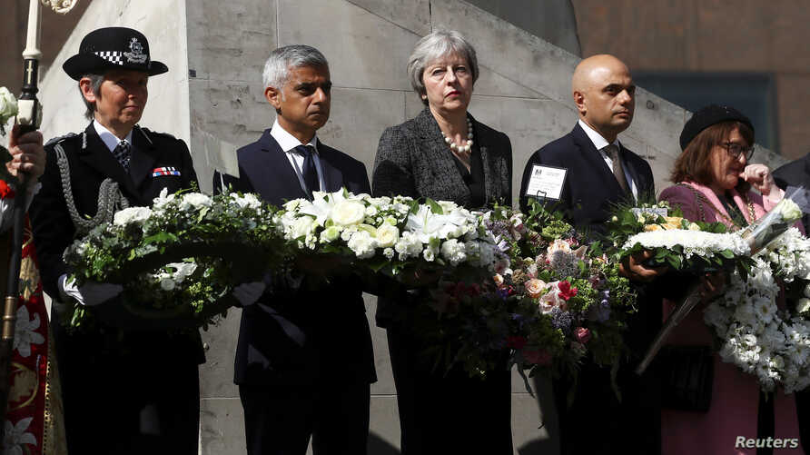 Britain's Prime Minister Theresa May, London's Mayor Sadiq Khan, Metropolitan Police Commissioner Cressida Dick and Home Secretary Sajid Javid hold wreaths during commemorations of the first anniversary of the attack on London Bridge, in London, Brit