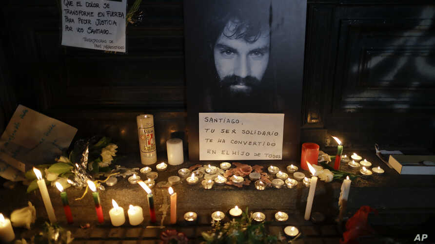 "A photo of missing activist Santiago Maldonado is surrounded by candles and a message that reads in Spanish: ""Santiago, your solidarity has made you the son of all,"" at a makeshift memorial outside the morgue, in Buenos Aires, Argentina, Oct. 20, 201"