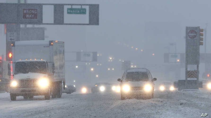 Vehicles drive drive through snow as they approach the Holland Tunnel, Feb. 9, 2017, in Jersey City, N.J.