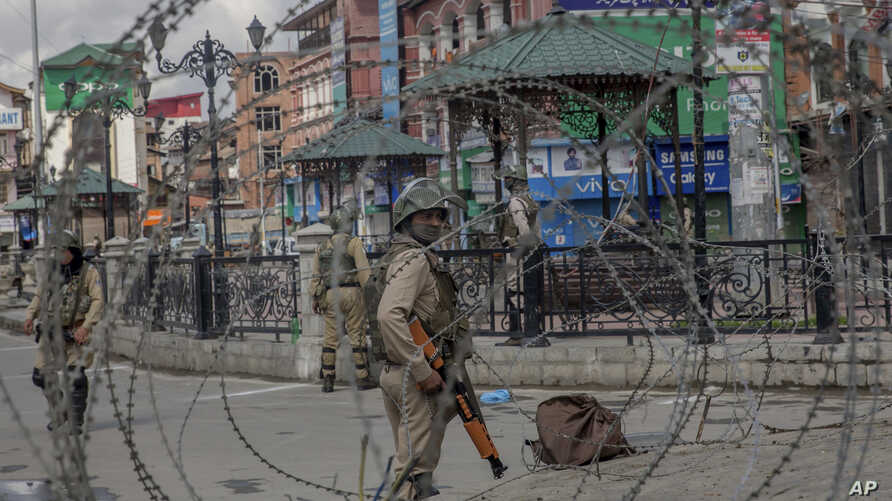 Indian Paramilitary soldiers are seen through barbed wire in Srinagar, Indian-controlled Kashmir, May 19, 2018.