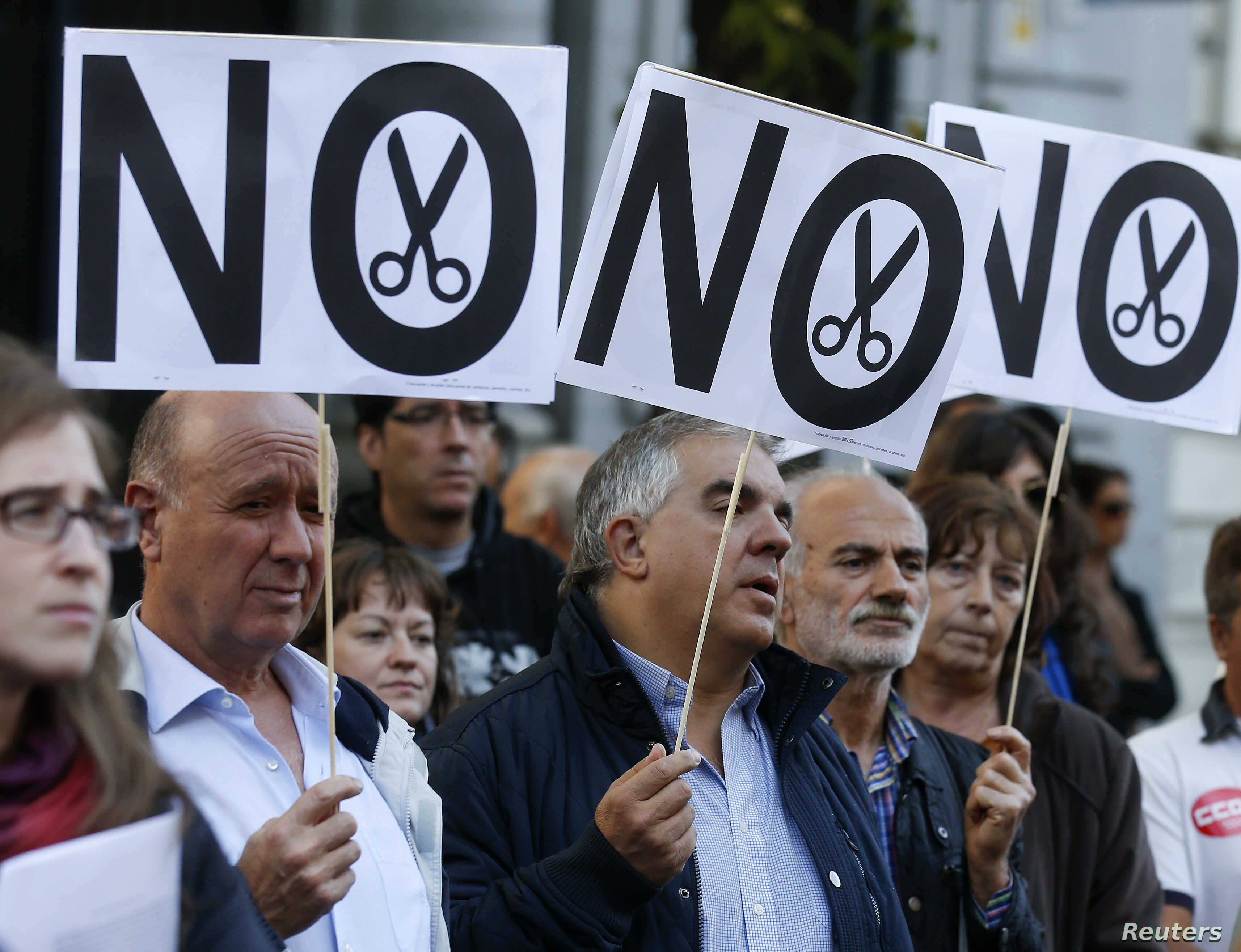 Demonstrators hold banners during a protest by trade unions against cuts in public universities in Madrid, October 23, 2012.