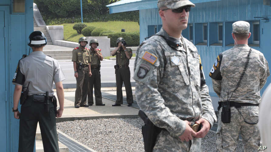In this July 27, 2014, file photo, North Korean army soldiers watch the south side while South Korean, left, and U.S. Army soldiers stand guard at the truce villages of Panmunjom in Paju, South Korea.