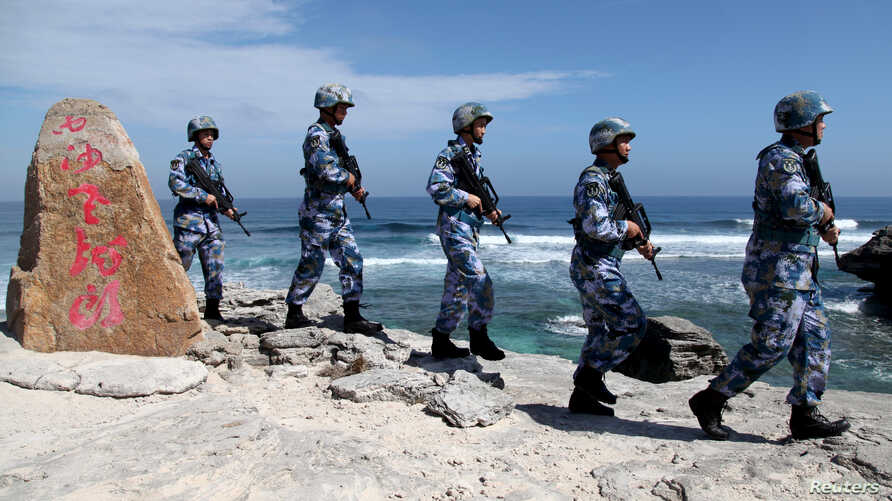 FILE - Soldiers of China's People's Liberation Army (PLA) Navy patrol at Woody Island, in the Paracel Archipelago in the South China Sea, Jan. 29, 2016.