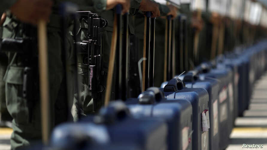 Venezuela's soldiers stand with cases of voting materials during a ceremony ahead of the regional elections which will be held on Oct, 15, in Caracas, Venezuela, Oct. 9, 2017.