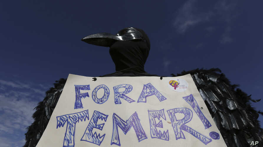 """A demonstrator dressed in a black feathered costume holds a sign telling Brazil's President Michel Temer to """"get out,"""" during an anti-government protest in Brasilia, Brazil, May 24, 2017."""
