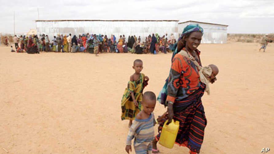 A woman walks with her children to a transit center in the Dolo Ado refugee camp in southern Ethiopia, July 19, 2011.