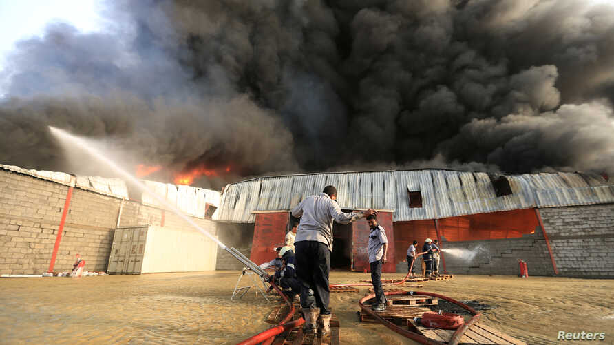 A crew battles a fire engulfing a warehouse of the World Food Program in Hodeida, Yemen, March 31, 2018.