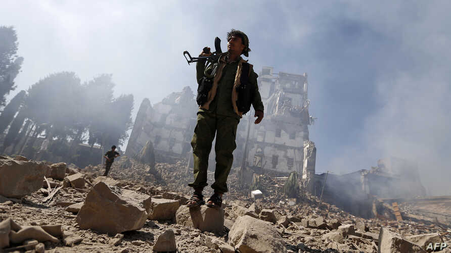 Houthi rebel fighters inspect the damage after a reported airstrike carried out by the Saudi-led coalition targeted the presidential palace in the Yemeni capital Sana'a, Dec. 5, 2017.