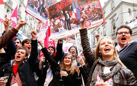 Supporters of Socialist Party candidate for the presidential election Francois Hollande celebrate with champagne after the first results of the second round of French presidential elections outside Socialist Party campaign headquarters in Paris, Fran