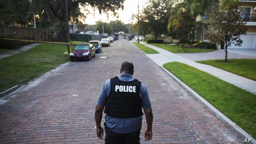 A police officer walks toward a crime scene in Florida. Four police officers were shot in two separate shootings in two Florida cities, Aug. 19, 2017.