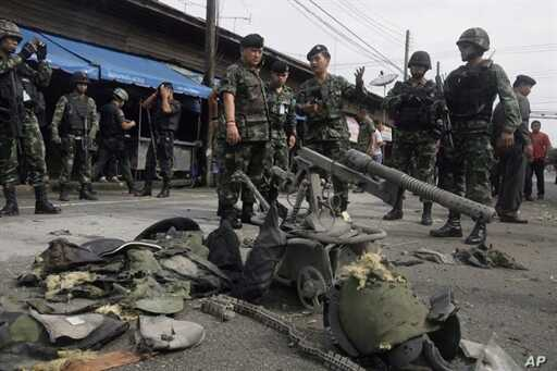 Thai bomb squad members and soldiers inspect the site of a failed bomb attack blamed by police on separatist insurgents in the Sungaipadi distrist of Thailand's restive southern province of Narathiwat, 1 Jan 2011