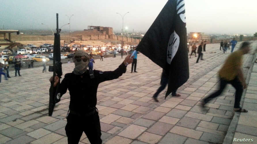 FILE - A fighter of the Islamic State of Iraq and the Levant (ISIL) holds an ISIL flag and a weapon on a street in the city of Mosul, June 23, 2014.