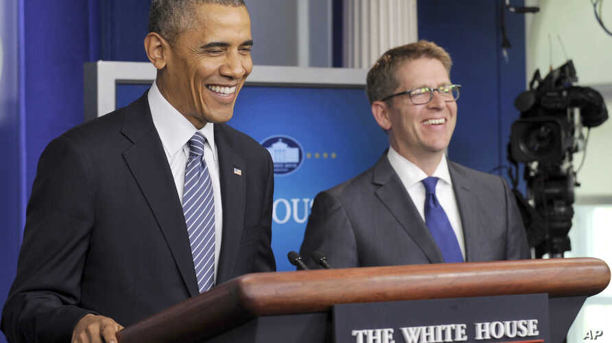 FILE - President Barack Obama, left, shares a laugh with White House press secretary Jay Carney, right, as the president makes a surprise visit to the Brady Press Briefing Room in Washington.