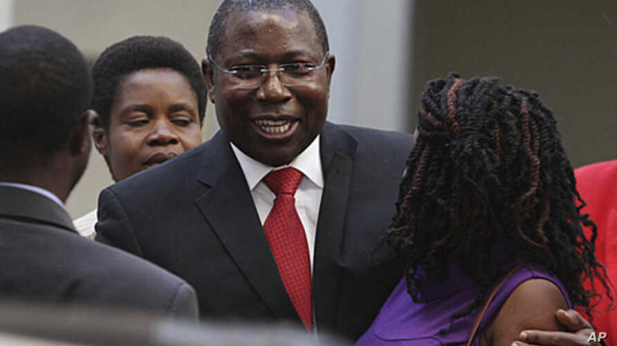 Energy and Power Development Minister Elton Mangoma (center) smiles with relatives at the High Court in Harare, June 28, 2011.
