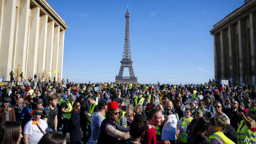 "French ""yellow vest"" protesters, with the Eiffel Tower in the background, rally in support of an older female activist injured in a recent confrontation with police, March 30, 2019, in Trocadero Square, in Paris."