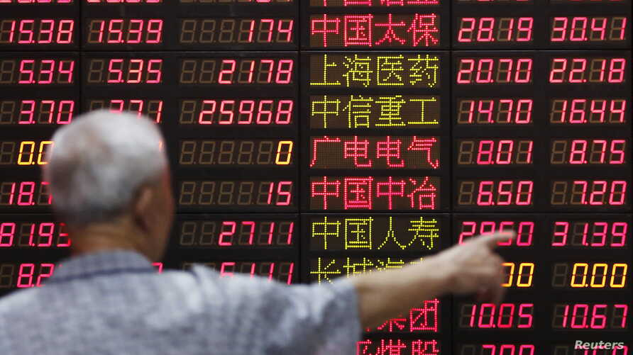 An investor looks at information displayed on an electronic screen at a brokerage house in Shanghai, China, June 30, 2015.
