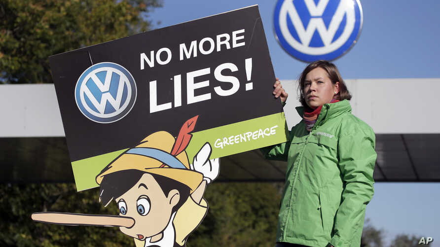 An activist of the environmental protection organization 'Greenpeace' holds a protest poster in front of a factory gate of the German car manufacturer Volkswagen in Wolfsburg, Germany, Sept. 25, 2015.