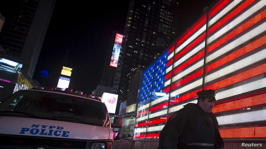 FILE - A New York police officer walks from a van that was deployed in Times Square to bolster security in the Manhattan borough of New York, Nov. 13, 2015.