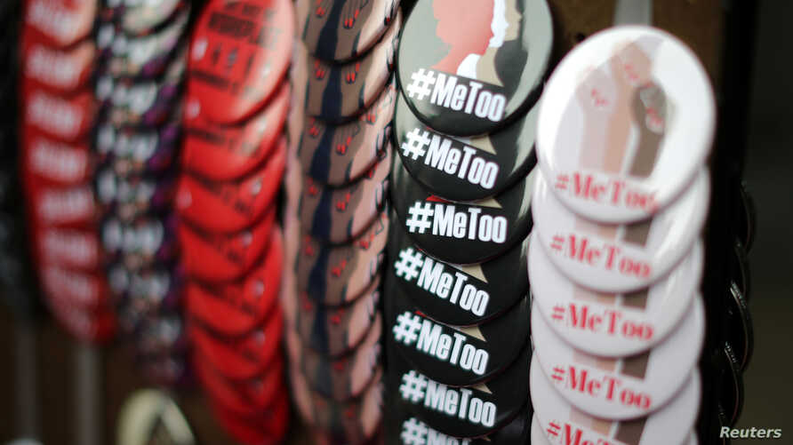 FILE - A vendor sells #MeToo badges a protest march for survivors of sexual assault and their supporters in the Hollywood section of Los Angeles, California, Nov. 12, 2017.