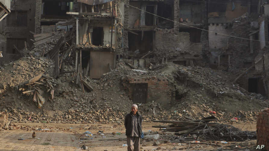 A Nepalese man walks past damaged houses one month after the deadly 7.8 magnitude earthquake in Kathmandu, Nepal, May 25, 2015.