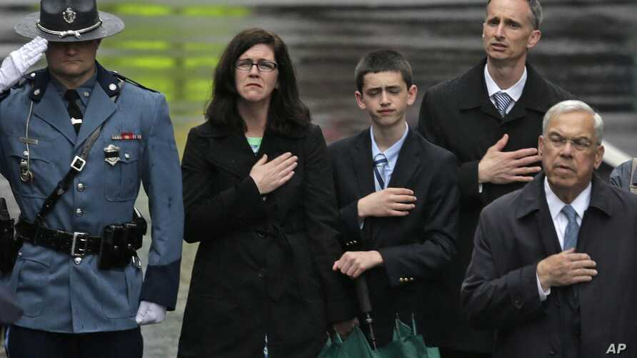 The family of Martin Richard, from left, mother Denise, brother Henry, and father Bill Richard, with former Boston Mayor Tom Menino, right, during a tribute in honor of the one year anniversary of the Boston Marathon bombings, Apr. 5, 2014, in Boston
