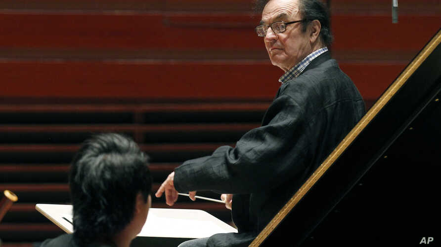 FILE - In this Oct. 19, 2011 file photo, world-renowned conductor Charles Dutoit, right, performs with the Philadelphia Orchestra. Four women have accused Dutoit of sexual misconduct that allegedly occurred on the sidelines of rehearsals or performan