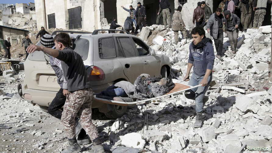 Residents carry an injured woman on a stretcher in a site hit by airstrikes in the rebel-controlled area of Maarat al-Numan town in Idlib province, Syria, Jan. 9, 2016.
