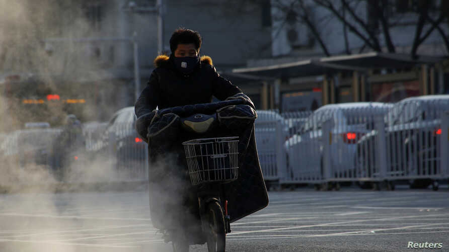 A man rides an electric scooter past steaming manhole covers on a cold day in Beijing, Dec. 1, 2017.