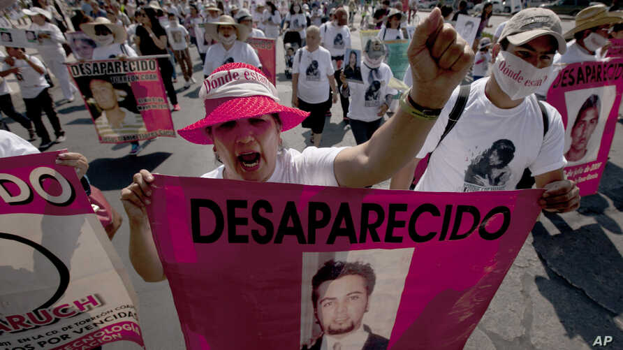 FILE - Mothers, relatives and friends march with banners and posters showing images of relatives that have been disappeared, during Mother's Day, in Mexico City.