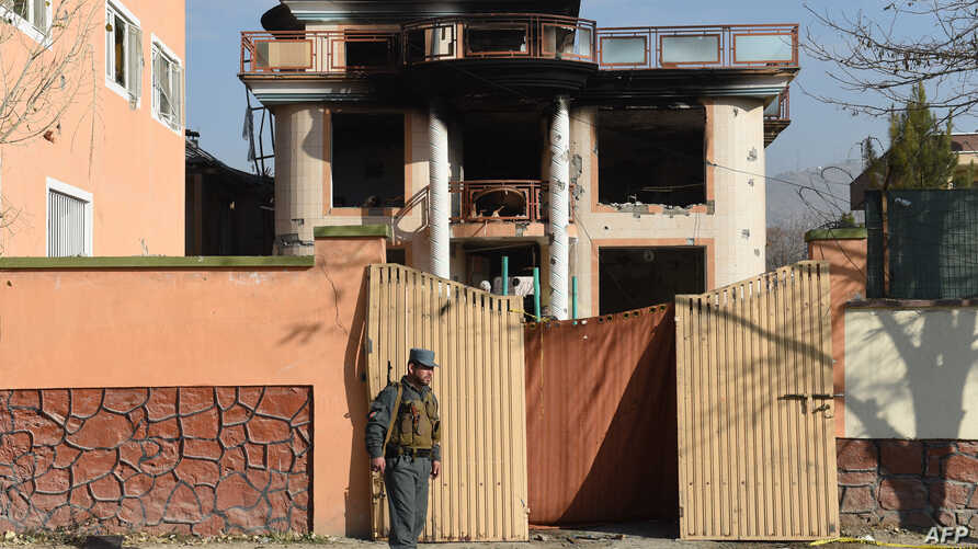 An Afghan policeman keeps watch at the gate of a foreign compound following an attack by Taliban militants in Kabul, Nov. 30, 2014.