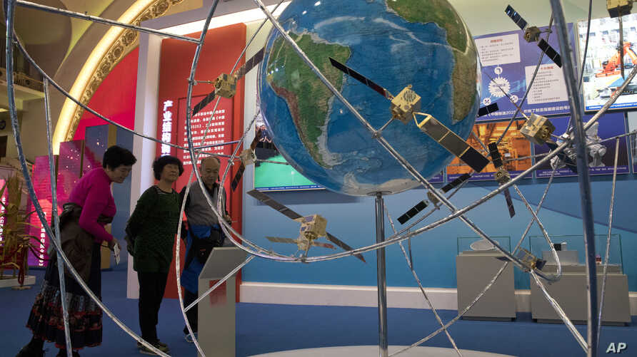 FILE - In this Oct. 19, 2017 photo, visitors look at a display of satellite technologies at an exhibition highlighting China's achievements under five years of Xi's leadership at the Beijing Exhibition Hall in Beijing, China.