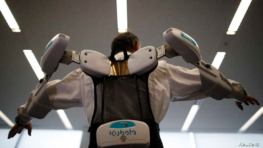 An employee of ActiveLink Co. established under the intrapreneurship of Panasonic Corp, demonstrates a robotic exoskeleton developed to help farmers and construction workers.
