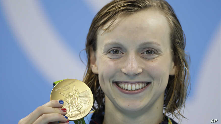 United States' Katie Ledecky shows off her gold medal after setting a new world record in the women's 400-meter freestyle final during the swimming competitions at the 2016 Summer Olympics, Aug. 8, 2016, in Rio de Janeiro, Brazil.