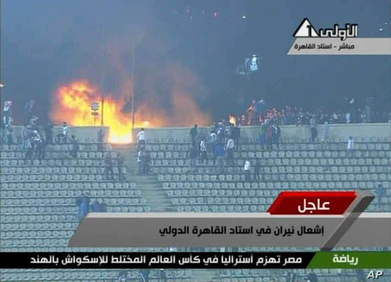 This image from Egypt TV shows fans and a fire at a soccer stadium in Port Said, Egypt, February 1, 2012. (AP)