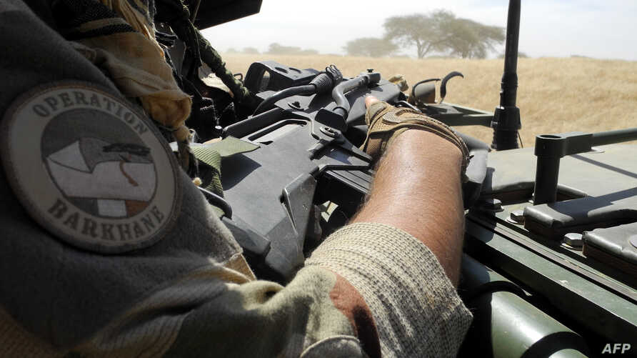 FILE - A soldier of France's Barkhane mission holds a weapon as he patrols in central Mali, in the border zone with Burkina Faso and Niger, Nov. 01, 2017. Two members of the French counterterrorism force in Mali were killed Wednesday in Mali, authori...