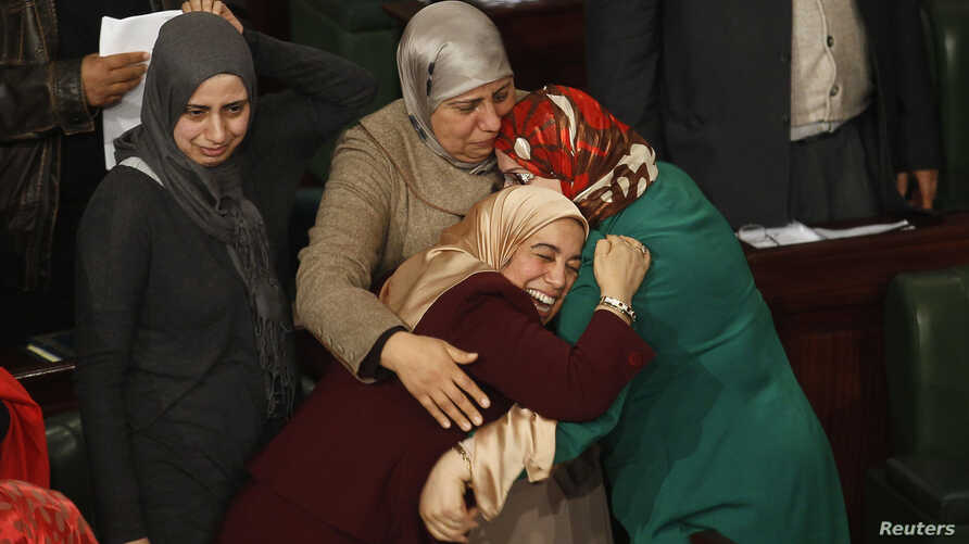 FILE - Members of the Tunisian parliament celebrate after approving the country's new constitution in the assembly building in Tunis January 26, 2014.
