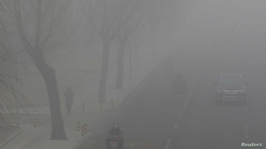 People drive and ride amid the smog in Beijing, Feb. 14, 2017. Beijing has greatly improved how it collects data, made more of it available to the public and cracked down on misreporting.