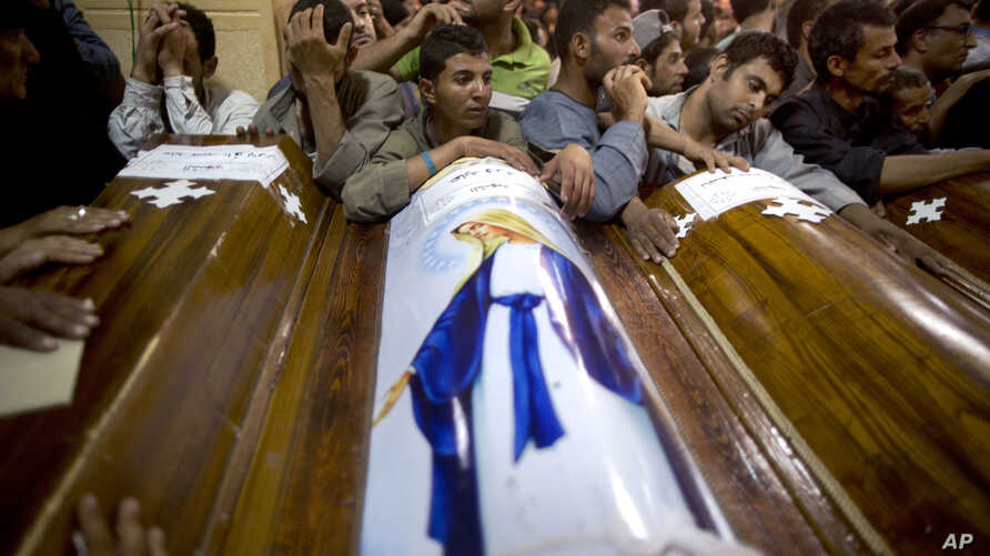 FILE - Relatives of Coptic Christians who were killed during a bus attack, surround their coffins, during their funeral service, at Abu Garnous Cathedral in Minya, Egypt, May 17, 2017. The Libya connection in the Manchester concert bombing and Friday
