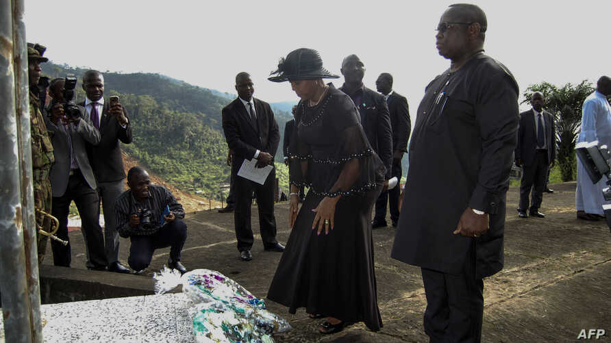 Sierra Leone's President Julius Maada Bio, right, and his wife, Fatima Bio, lay flowers on Aug. 14, 2018, at the commemoration site for the victims of last year's mudslide in Freetown.